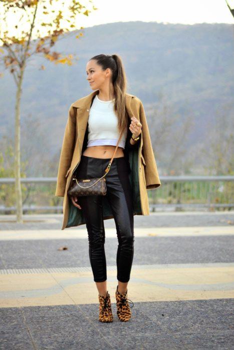 mujer con crop top blanco y abrigo