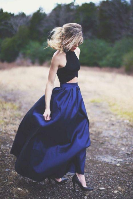 mujer con top negro y falda larga azul