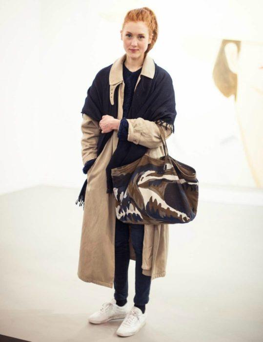 mujer pelirroja con saco y bolsa
