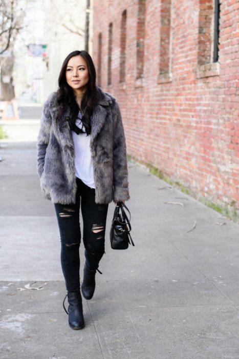 mujer con pantalon de mezclilla y abrigo de piel