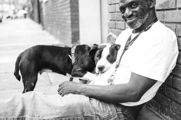 Hombre sentado abrazando a su perro
