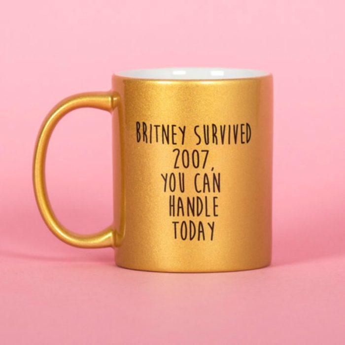 taza dorada con cita y fondo rosa