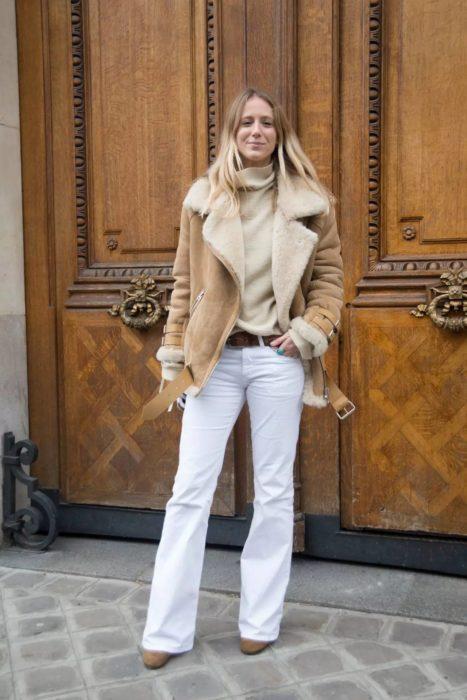 mujer con chamarra de borrego y pantalones blancos