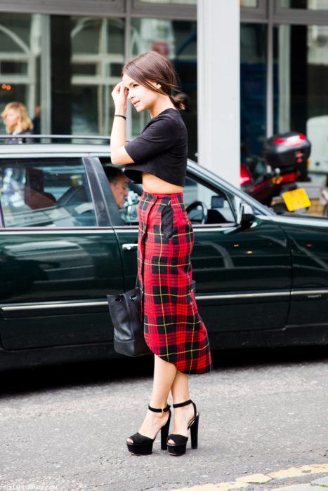 mujer con top negro y falda roja de cuadros