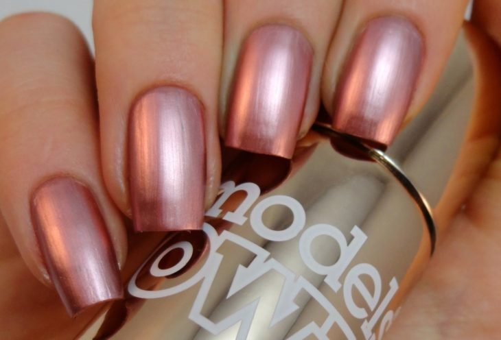 manos con uñas de color rosa metalico