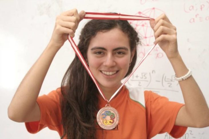 mujer con el cabello largo cargando una medalla