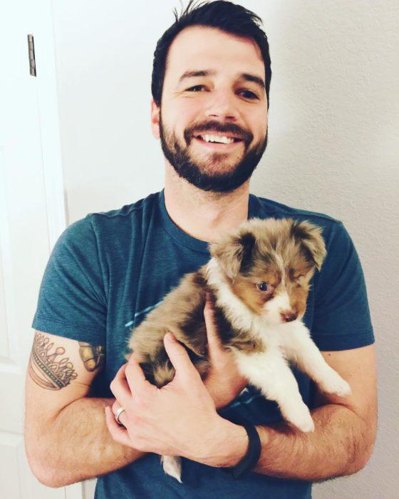 hombre sonríe y carga a perro sin un ojo