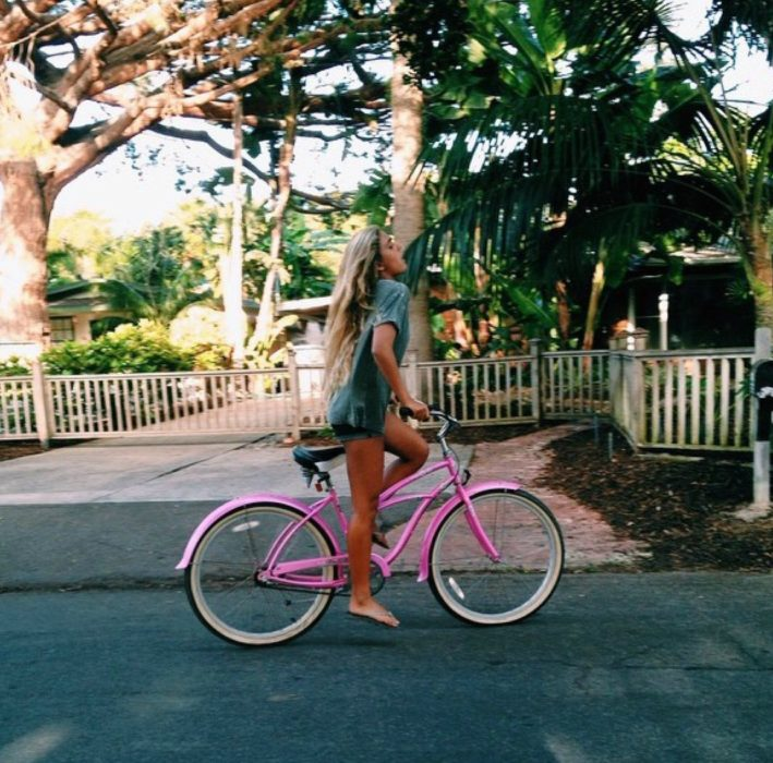 mujer en bicicleta rosa