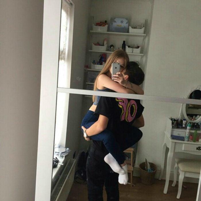 hombre cargando a mujer y foto en el espejo