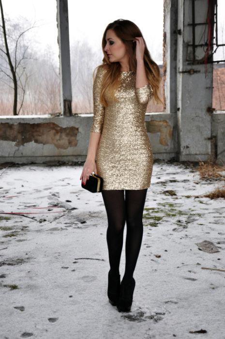 Chica usando un vestido largo de lentejuelas, medias y zapatos negros