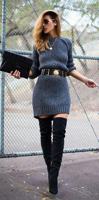 Chicausando un vestido color fris con un cinturón dordo y botas negras
