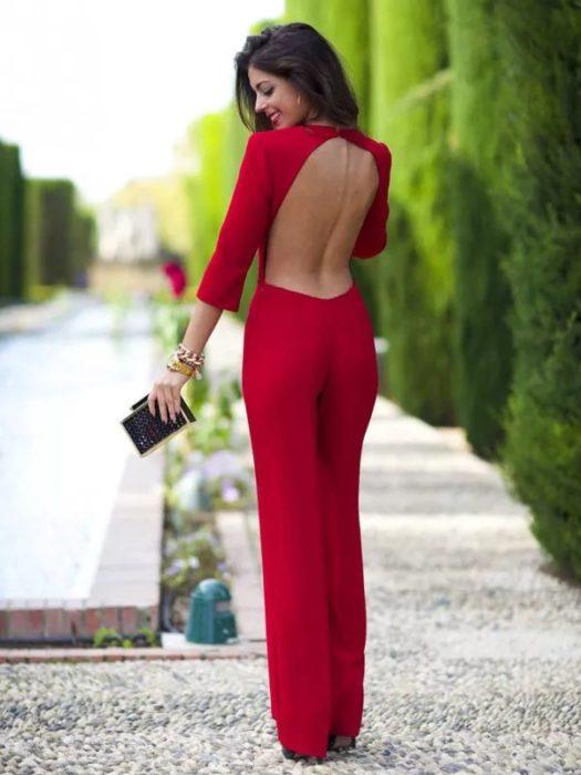 Chia usando un palazo color rojo y la espalda descubierta