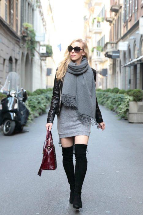 mujer con vestido gris, botas y bufanda