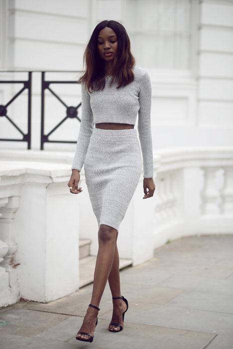 mujer morena con top y falda gris