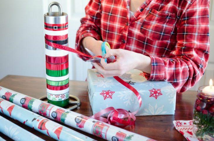 mujer envolviendo regalos con papel y moños