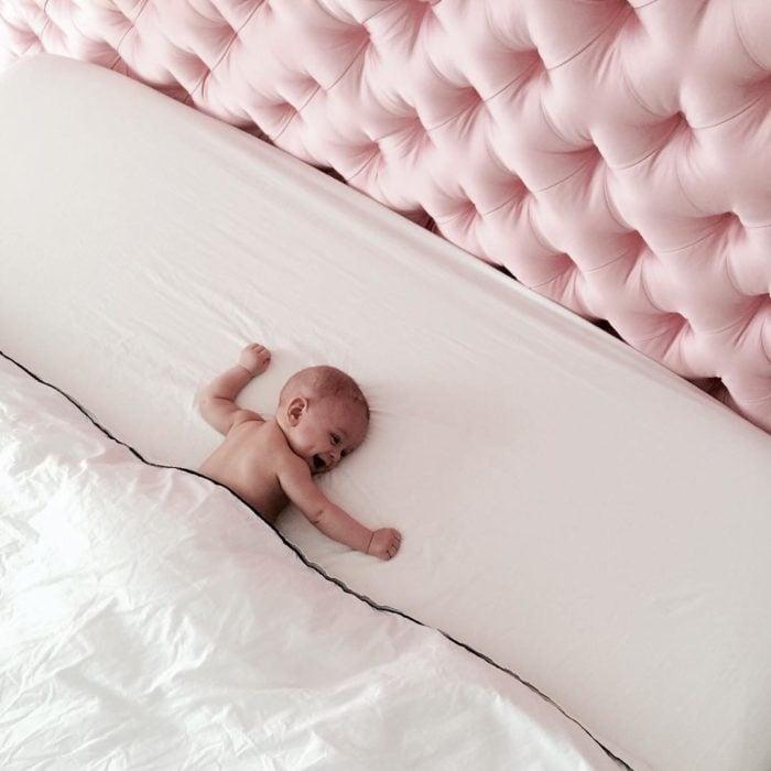 bebe acostado en cama con respaldo rosa