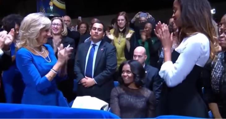 mujer sentada y personas le aplauden