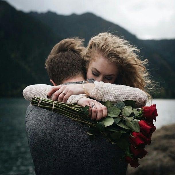 Chica abrazando a un chico cuando le regala flores