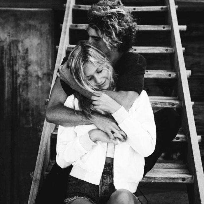 Chico abrazando a una chica mientras están en las escaleras