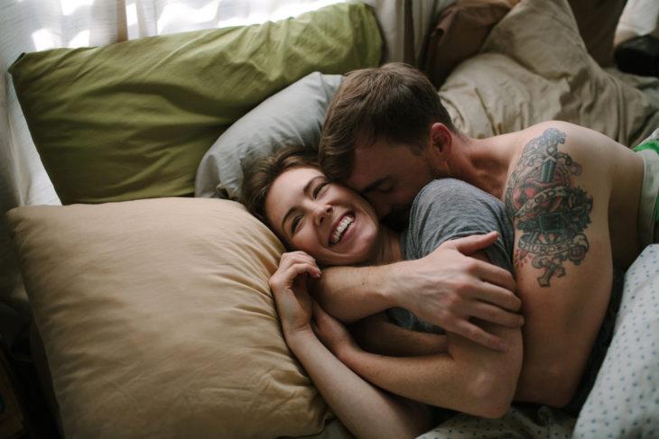 Pareja de novios recostados en la cama abrazados
