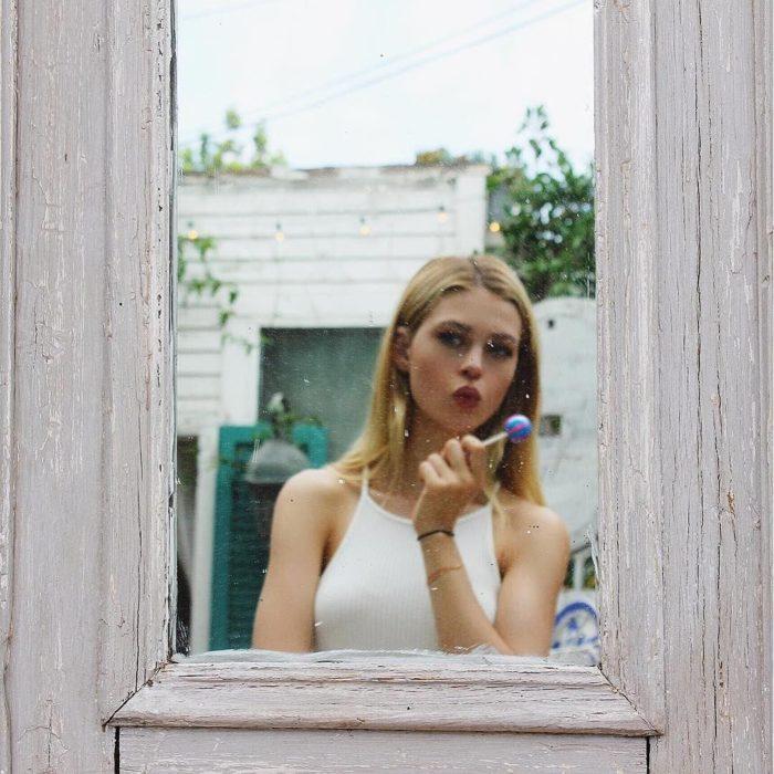 mujer rubia se mira al espejo con paleta