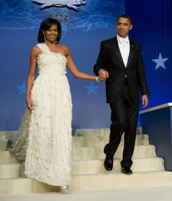 Michelle obama usando un vestido de color blanco en un baile