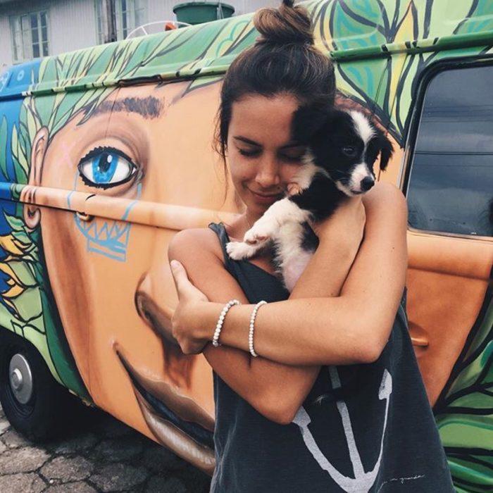 chica cargando perro pequeñlo