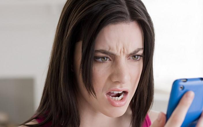 chica enojada viendo su movil