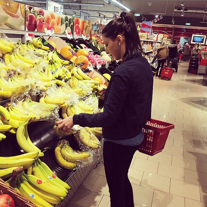 mujer en super mercado comprando platanos