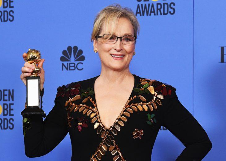 mujer rubia con lentes y premio