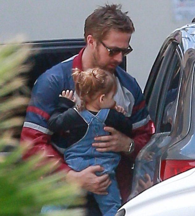 hombre cargando a niña en coche