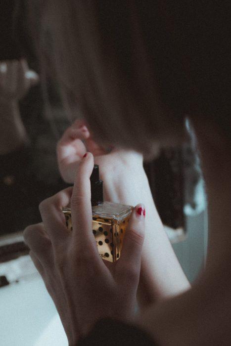 mujer rociándose perfume en la muñeca