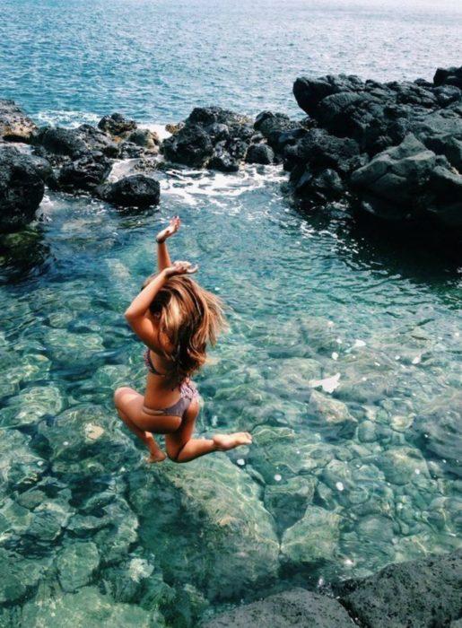 mujer rubia saltando a rio