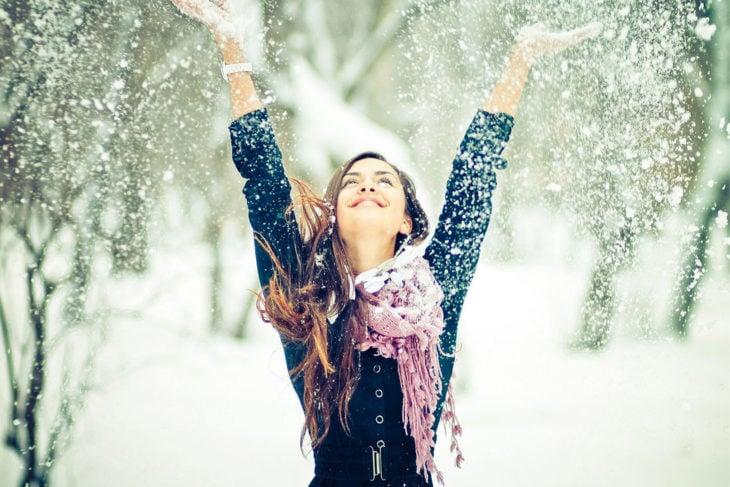 mujer feliz avienta nieve hacia arriba