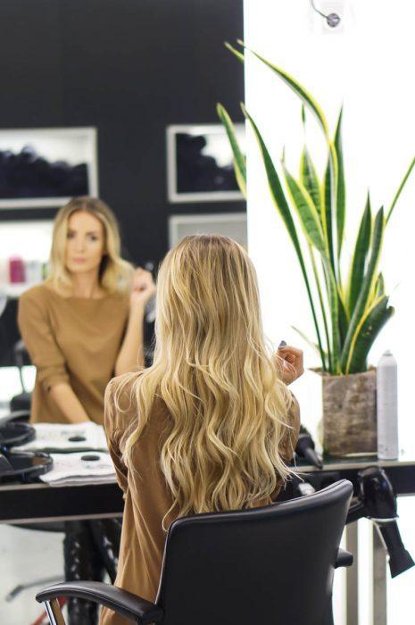 mujer rubia sentada frente el espejo