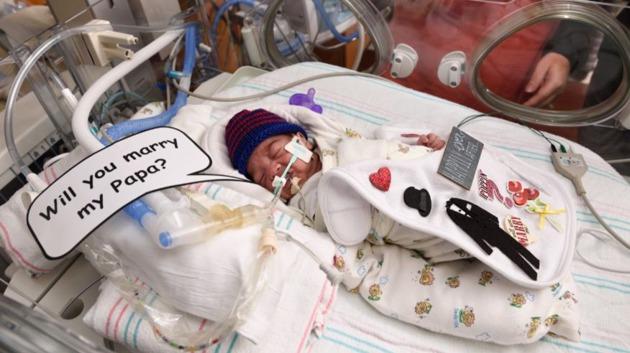 Bebé prematuro con un cartel de propuesta de matrimonio para su mamá