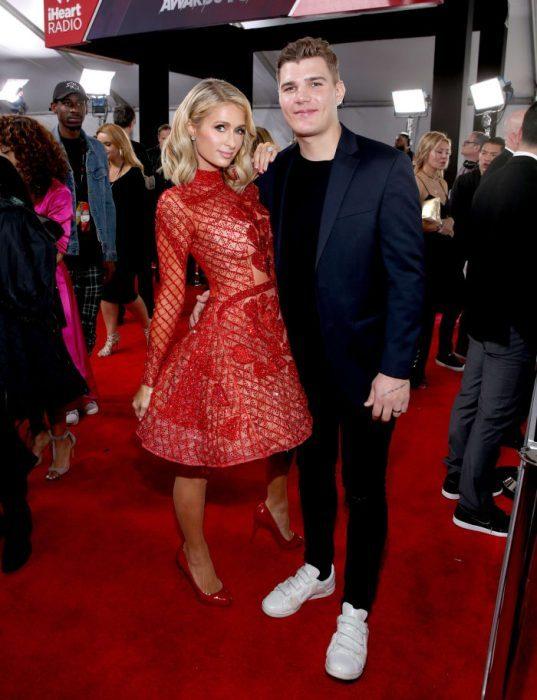 Paris Hilton junto a su novio en una pasarlea de modas