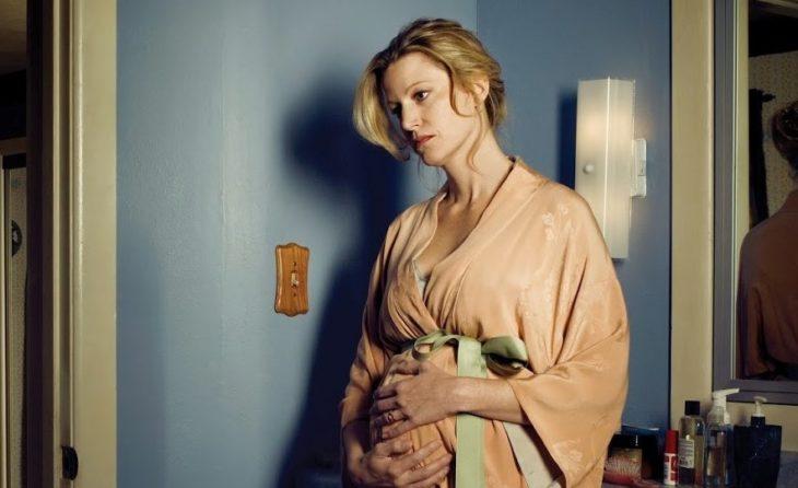 mujer rubia triste tocando vientre de embarazo
