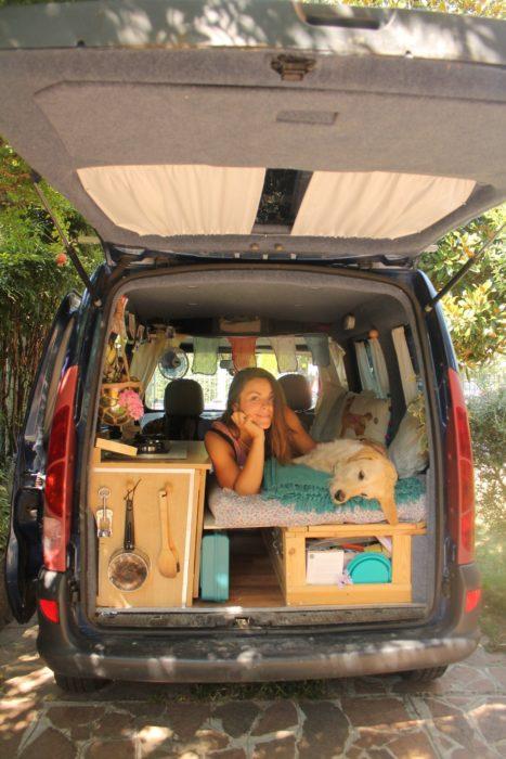 chica sentada en la parte trasera de una camioneta junto a su mascota