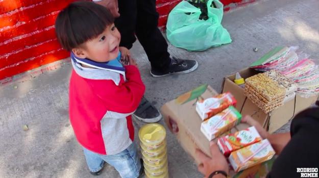 Niño de la calle recibiendo despensa de alimentos