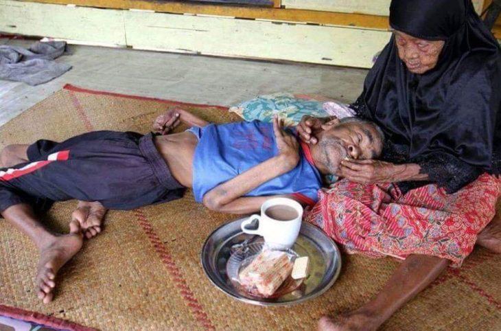 mujer anciana le da de comer a hombre