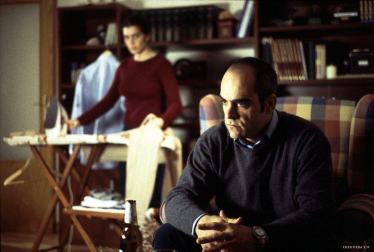 Hombre sentado en el sofá mientras su esposa plancha ropa