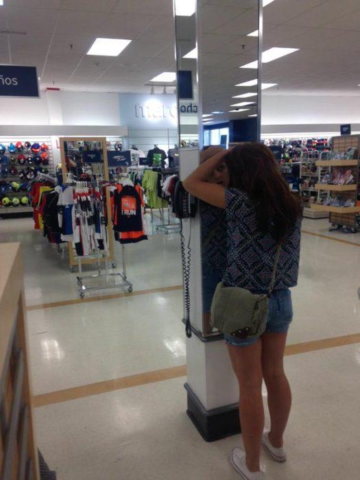 Chica apretando sus granitos frente al epejo de una tienda departamental