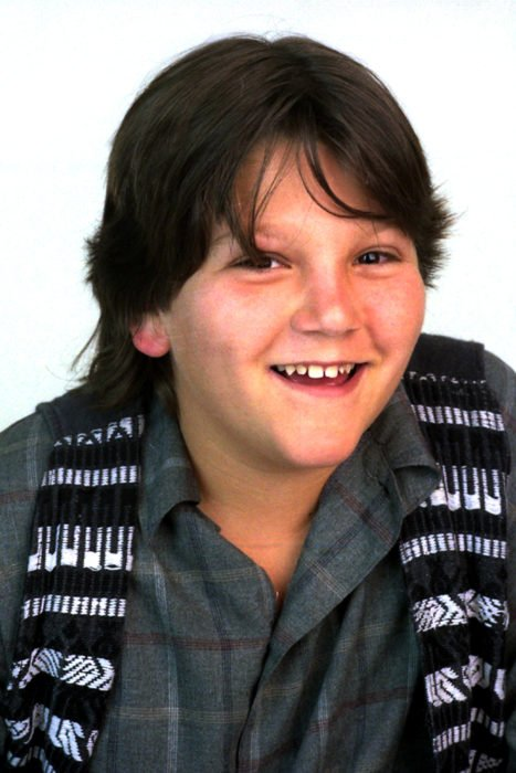 niño con cabello largo sonriendo