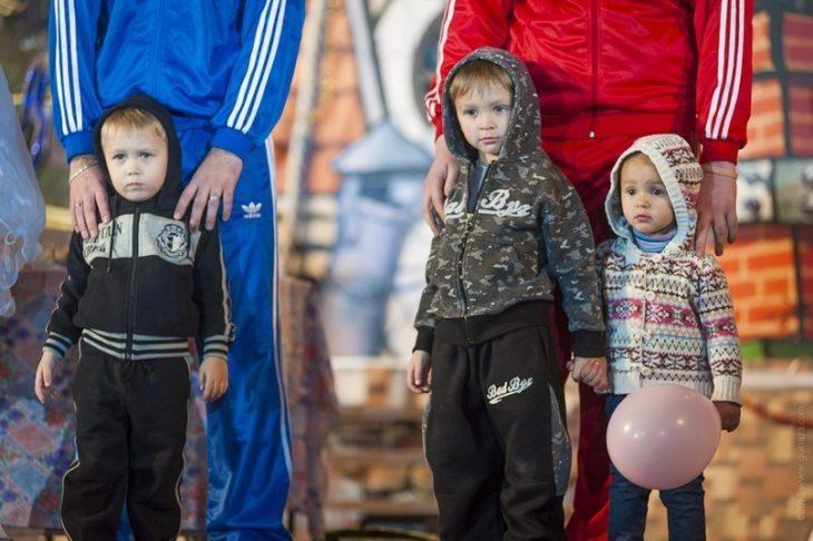 Niños parados junto a sus padres