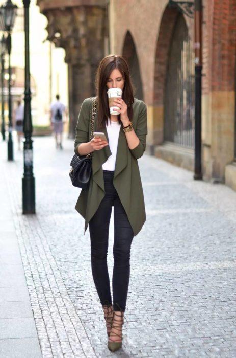 Chica caminando por la calle y bebiendo café