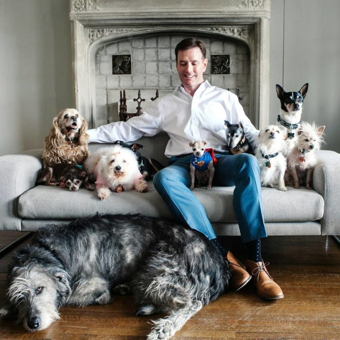 HOmbre sentado junto a sus perros
