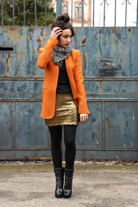 chica con falda de lentejuelas y abrigo naranja