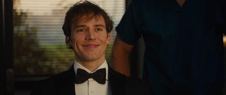 hombre con traje y moño sonriendo