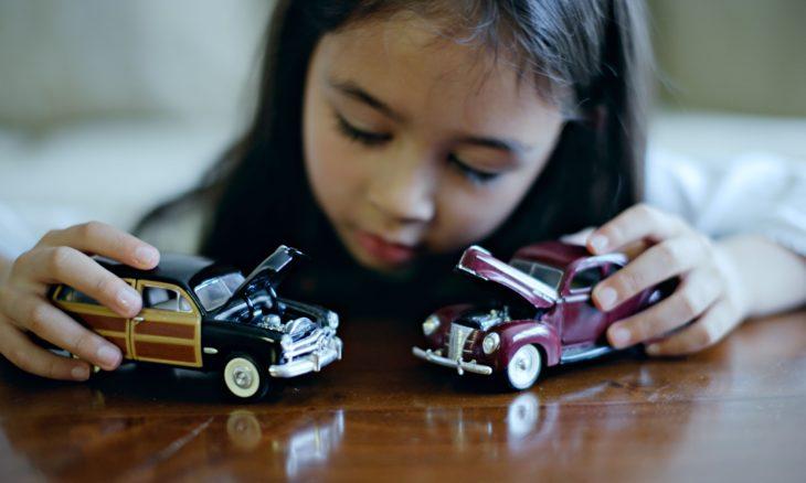niña jugando con carros